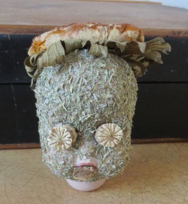 Poison Child (porcelain doll head, powdered wormwood, aconite leaves, amanita muscaria cap, poppy pods, mandrake root)